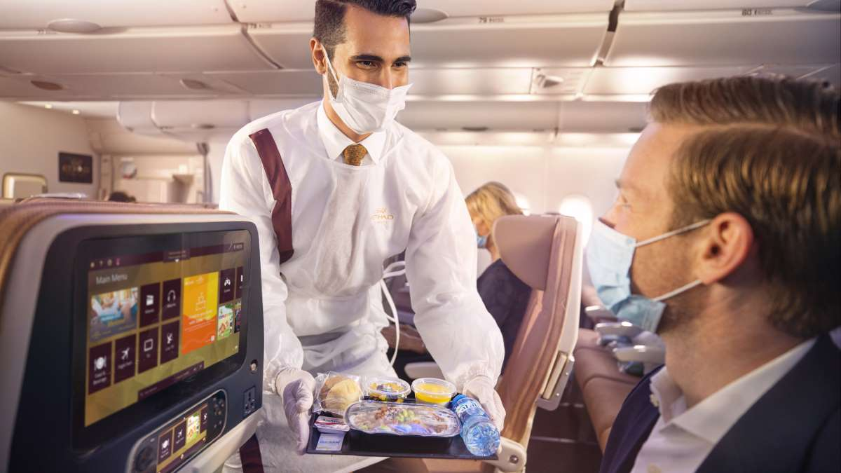 Etihad-Crew-onboard-with-PPE-serving-guests.jpg