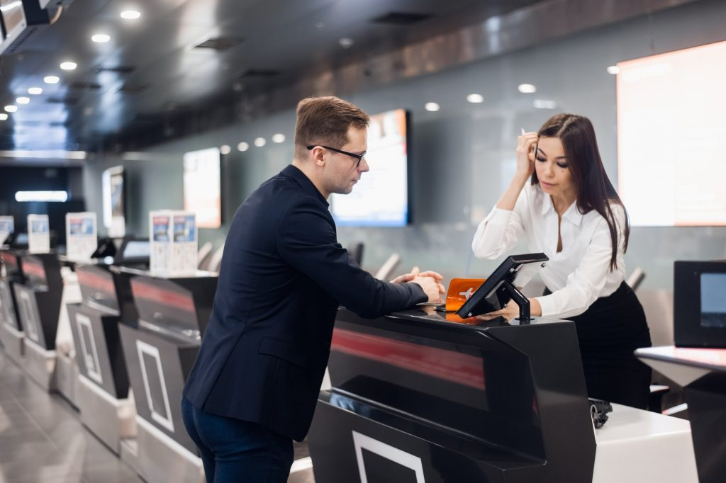 staff-at-airport-check-in-desk-handing-ticket-to-businessman-1024x682-1.jpg